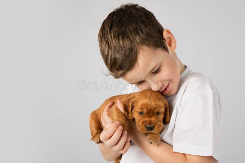 Jongen met rood die puppy op witte achtergrond wordt geïsoleerd De Vriendschap van het jong geitjehuisdier stock fotografie