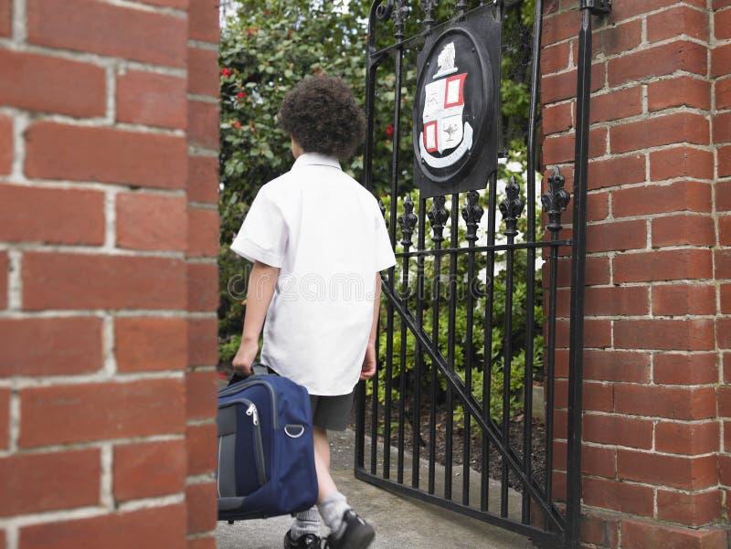 Jongen met Rugzak die Schoolpoort ingaan stock foto's