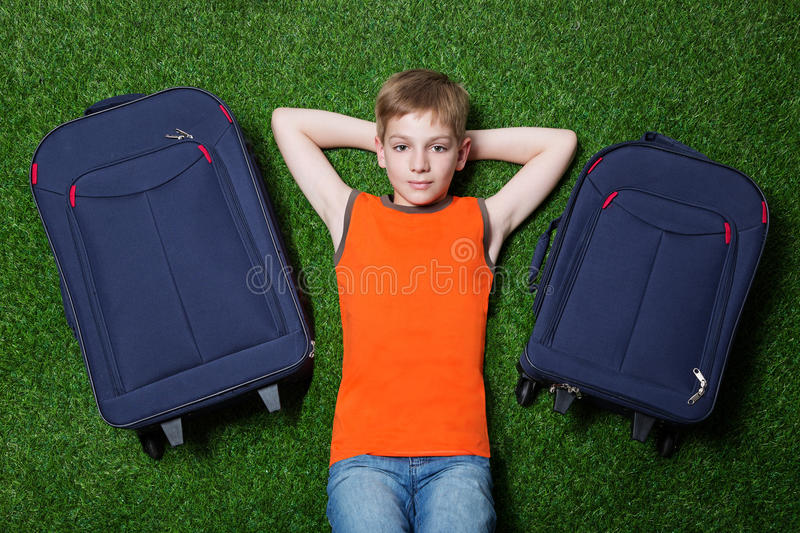 Jongen met siutcasesth die op groen gras liggen royalty-vrije stock foto's