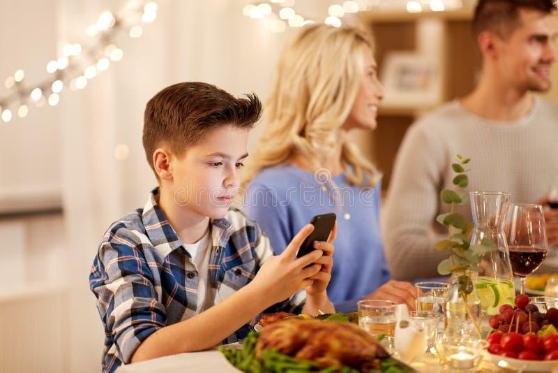 Jongen met smartphone bij de partij van het familiediner royalty-vrije stock foto