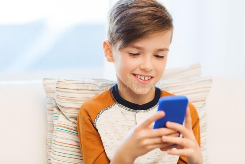 Jongen met of smartphone die thuis texting spelen stock fotografie