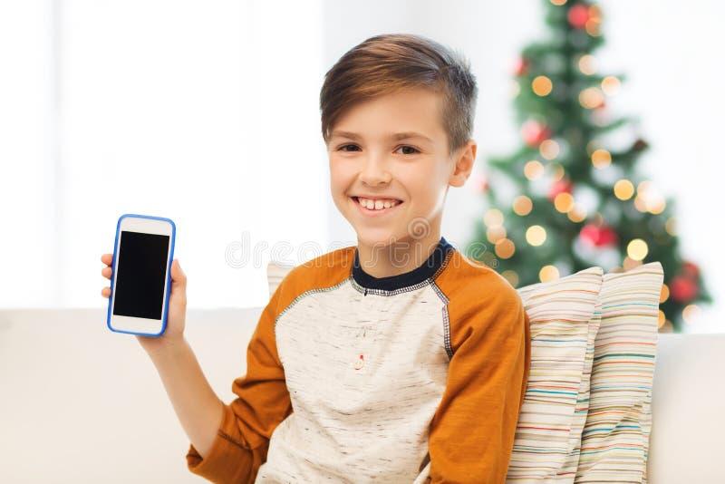 Jongen met smartphone thuis bij Kerstmis royalty-vrije stock afbeelding