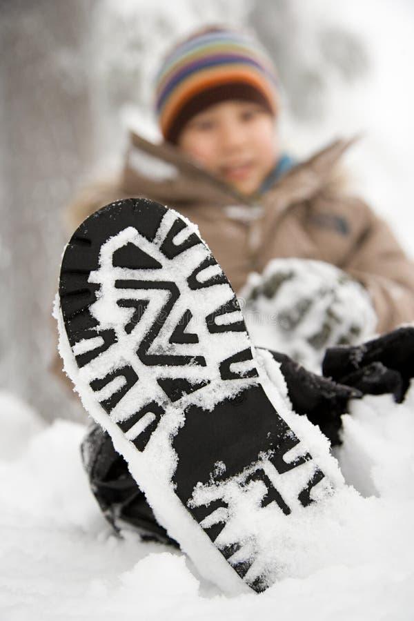 Jongen met sneeuw op zijn schoen stock foto