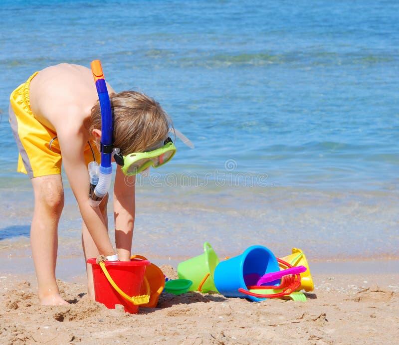 Jongen met speelgoed op het strand royalty-vrije stock afbeeldingen