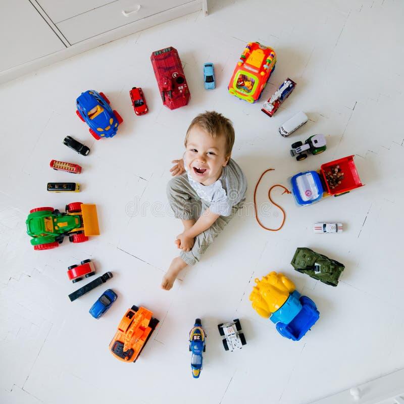 Jongen met stuk speelgoed auto's stock fotografie