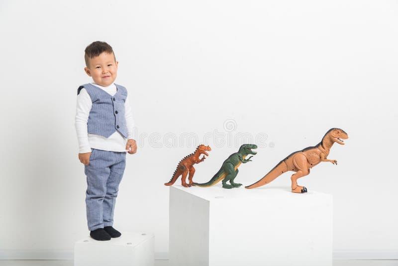 Jongen met stuk speelgoed dinosaurussen op witte achtergrond, baby Aziaat stock afbeelding