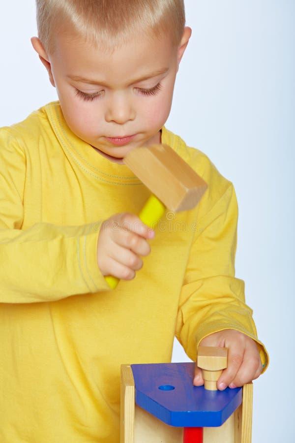Jongen met stuk speelgoed hamer stock foto's