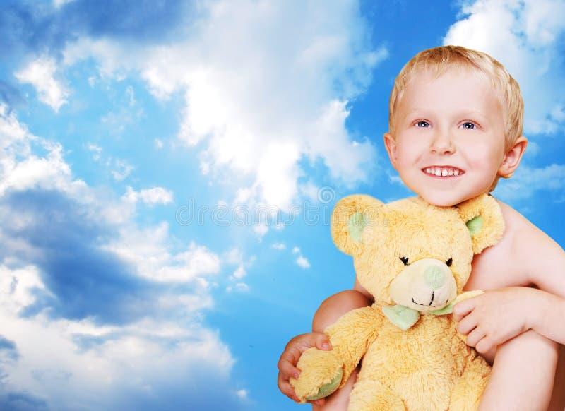 Jongen met teddybeer op blauwe hemel royalty-vrije stock fotografie