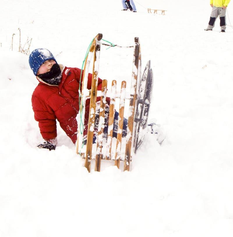 Jongen met toboggan in snow-covered landschap royalty-vrije stock afbeeldingen