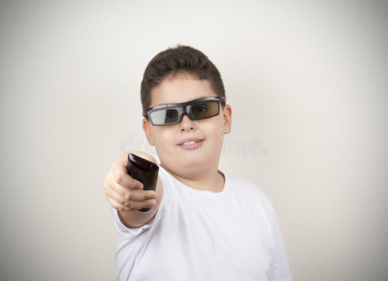 Jongen met TV-Afstandsbediening en 3d Glazen stock fotografie