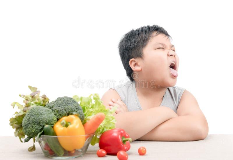 Jongen met uitdrukking van afschuw tegen groenten royalty-vrije stock fotografie