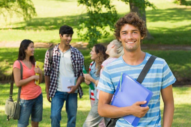 Jongen met universiteitsvrienden op achtergrond bij campus stock foto