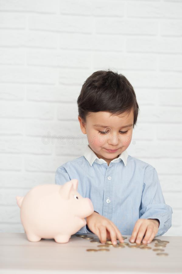 Jongen met varkensspaarvarken kinderjaren, geld, investering en gelukkig mensenconcept royalty-vrije stock afbeeldingen