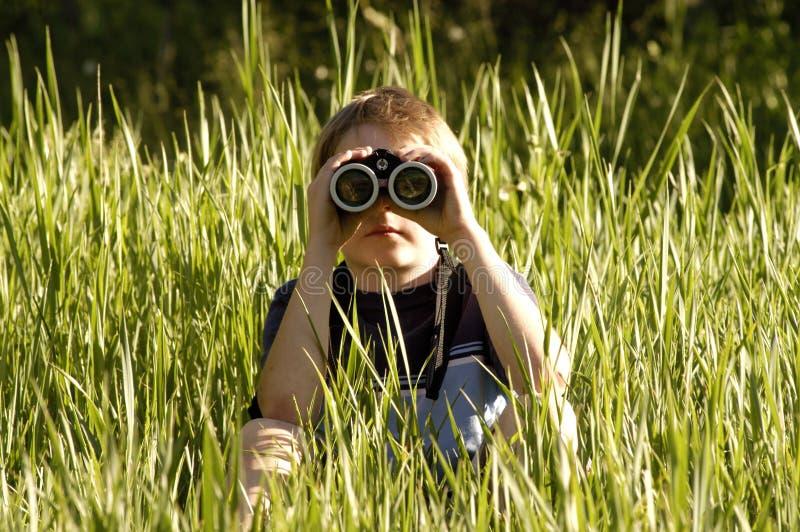 Jongen met verrekijkers van voorzijde stock fotografie
