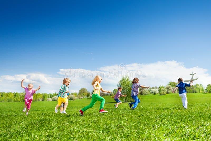 Jongen met vliegtuigstuk speelgoed en jonge geitjesrij die daarna lopen stock foto