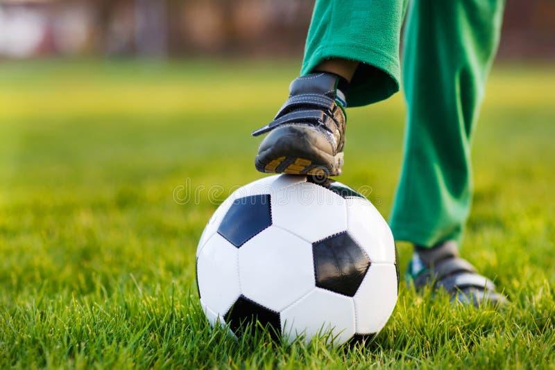 jongen met voetbal op voetbalgebied, in openlucht stock foto
