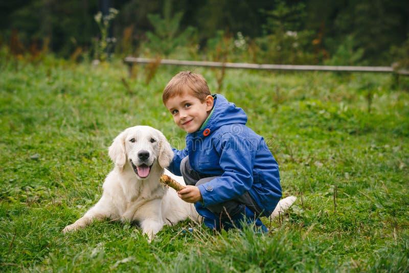 Jongen met zijn huisdier in het bos stock fotografie