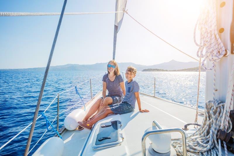 Jongen met zijn moeder aan boord van varend jacht op de zomercruise royalty-vrije stock afbeeldingen