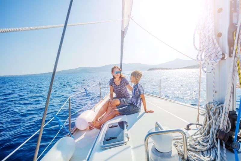 Jongen met zijn moeder aan boord van varend jacht op de zomercruise stock afbeelding
