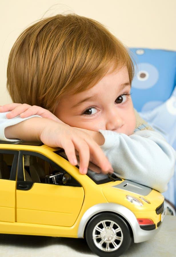 Jongen met zijn stuk speelgoed auto stock foto