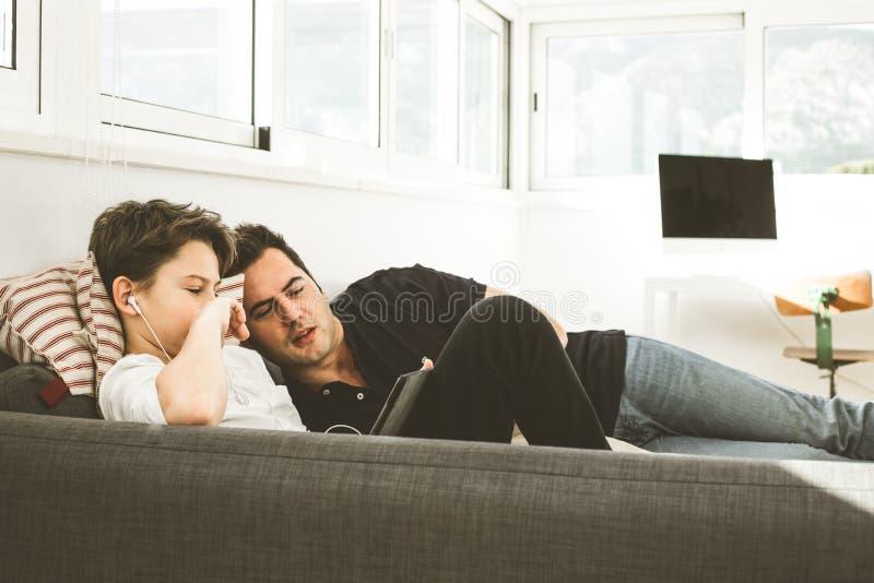 Jongen met zijn vader die een tablet op de laag bekijken Conceptenvader en kind met technologie royalty-vrije stock afbeelding