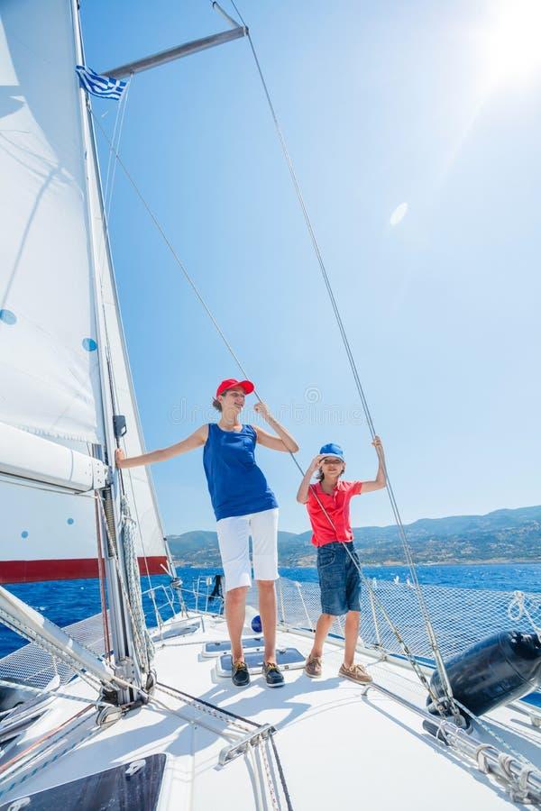 Jongen met zijn zuster aan boord van varend jacht op de zomercruise Reisavontuur, zeilen met kind op familievakantie royalty-vrije stock foto's