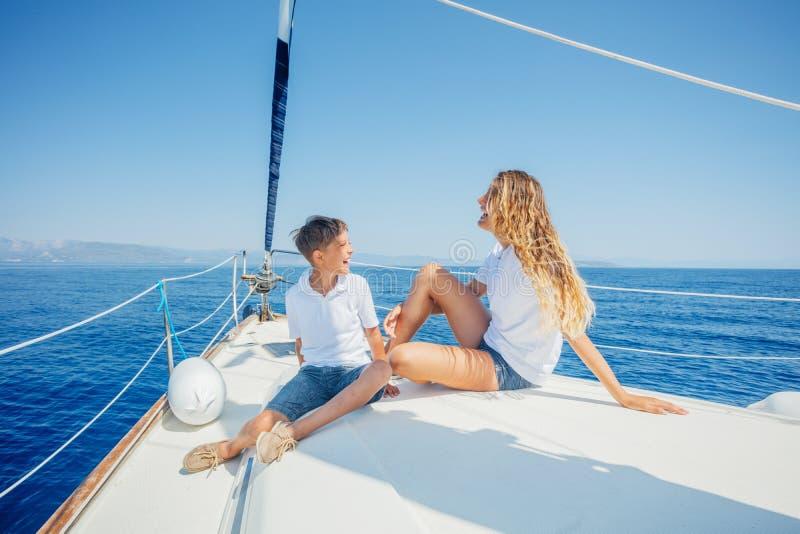 Jongen met zijn zuster aan boord van varend jacht op de zomercruise royalty-vrije stock afbeeldingen
