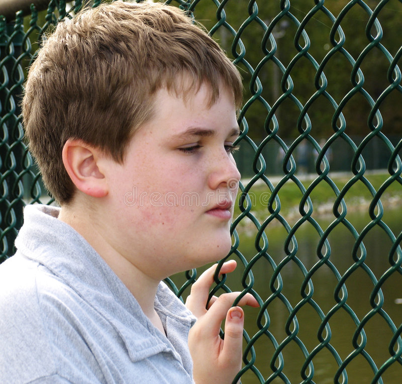 Jongen in omheining stock fotografie