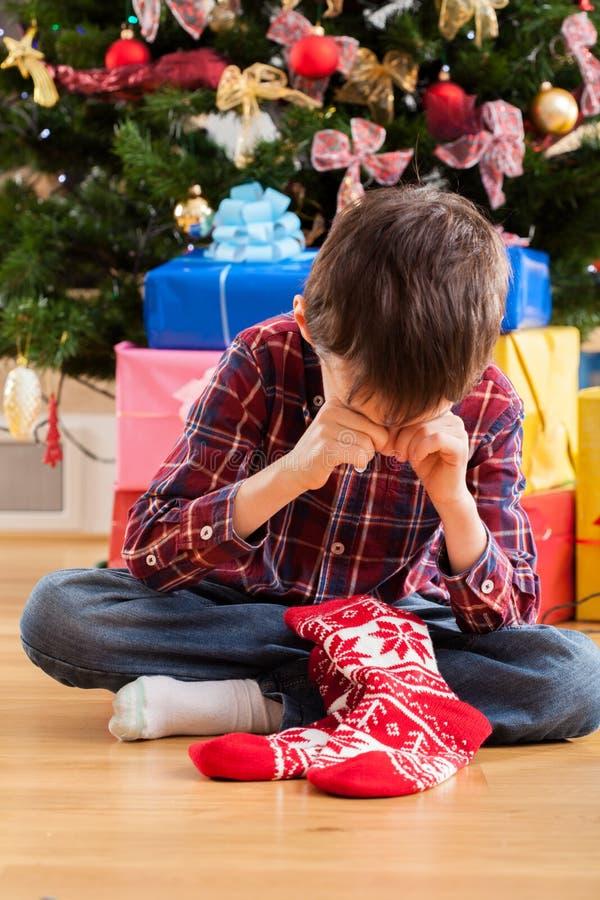 Jongen ontevreden met aanwezige Kerstmis stock afbeeldingen