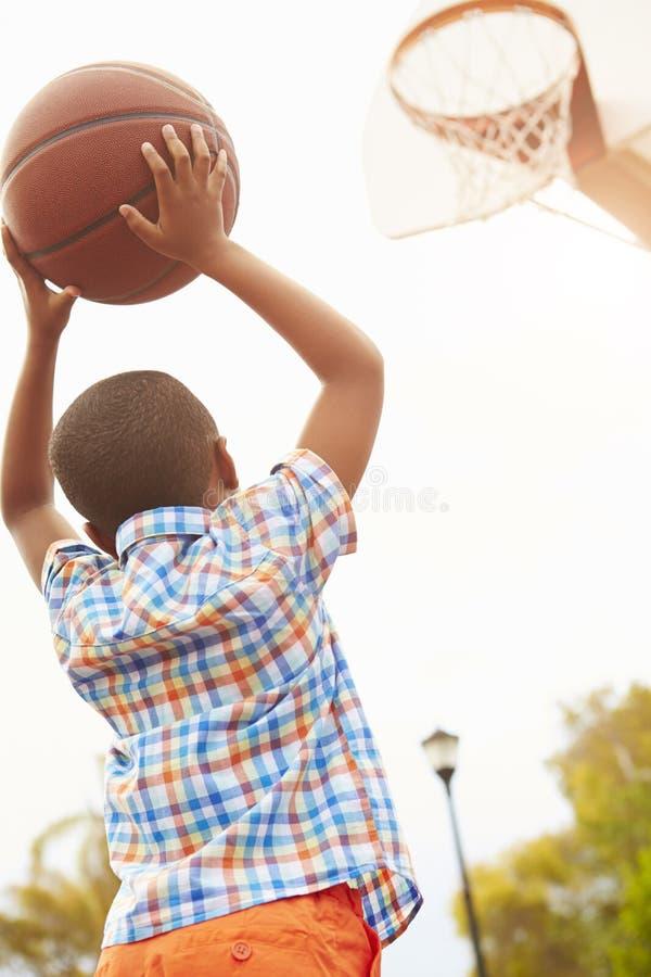 Jongen op Basketbalhof die voor Mand schieten stock afbeeldingen