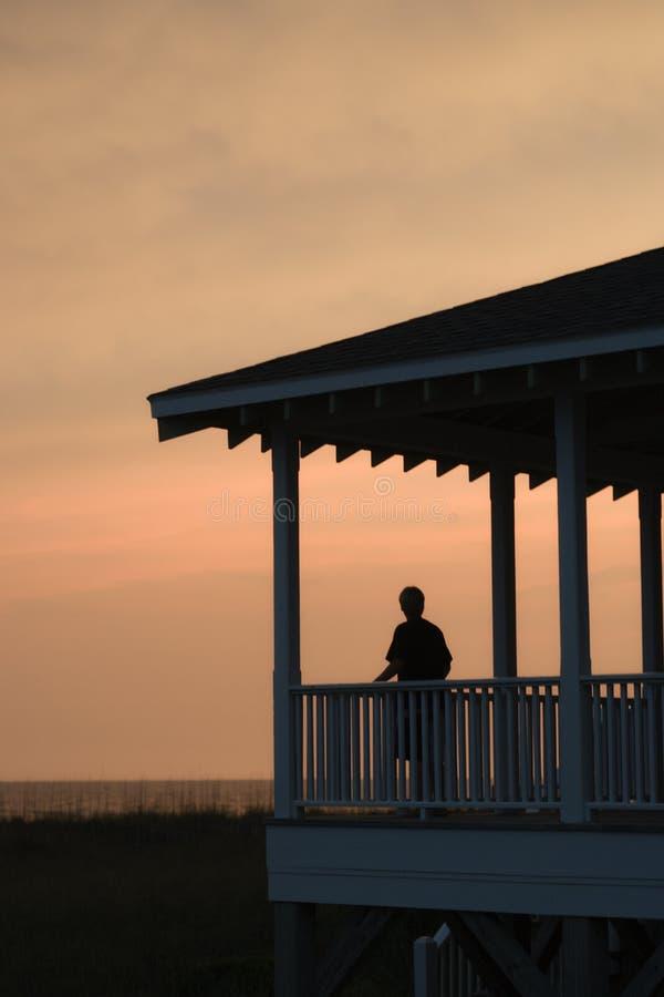 Jongen op beachfrontportiek stock afbeelding
