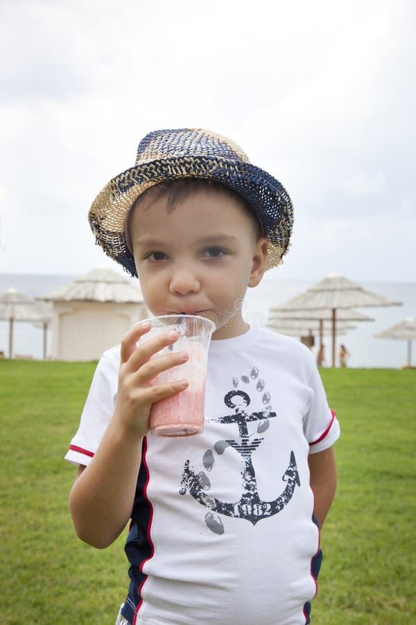 Jongen op de strand het drinken cocktail stock afbeelding