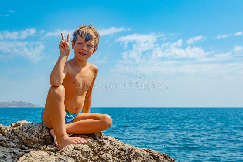 Jongen op de strandstenen tegen de achtergrond van duidelijk zeewater stock foto