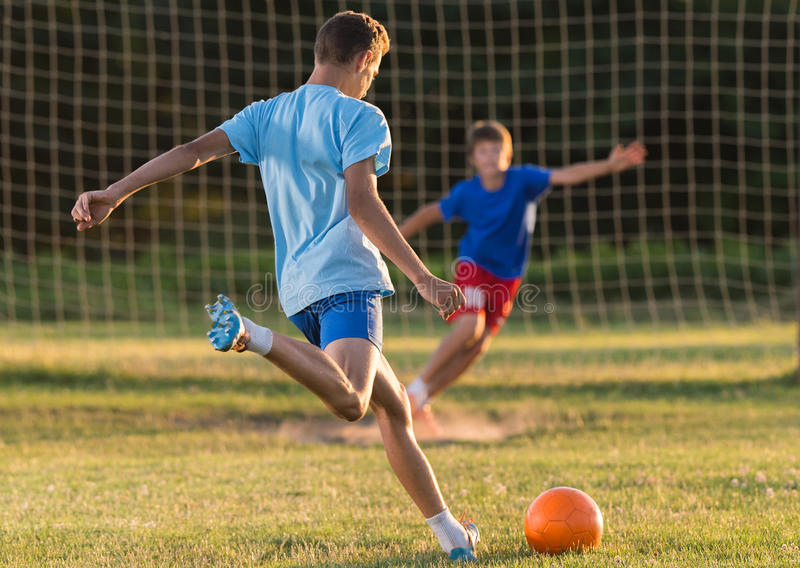 Jongen op de voetbal opleiding stock afbeelding