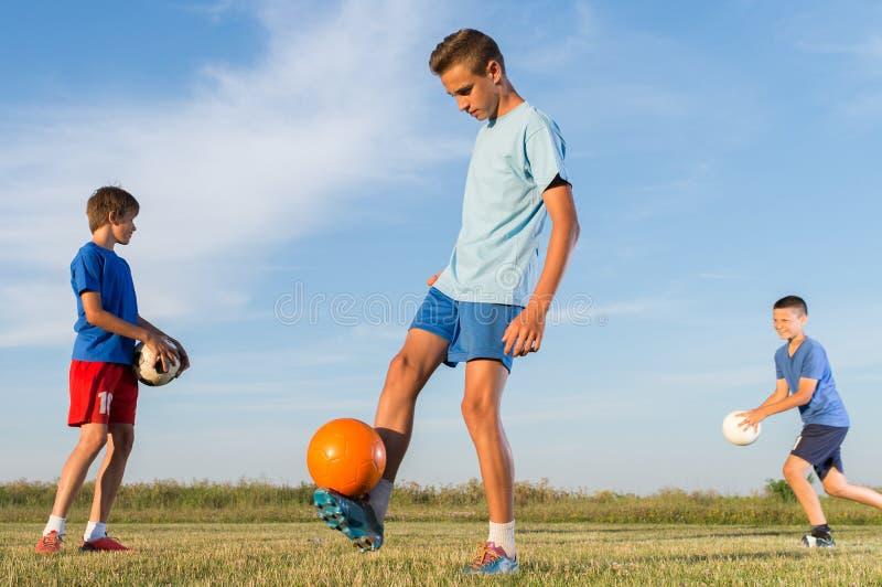 Jongen op de voetbal opleiding stock foto's