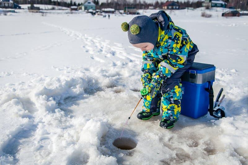 Jongen op een de winter visserij stock afbeeldingen
