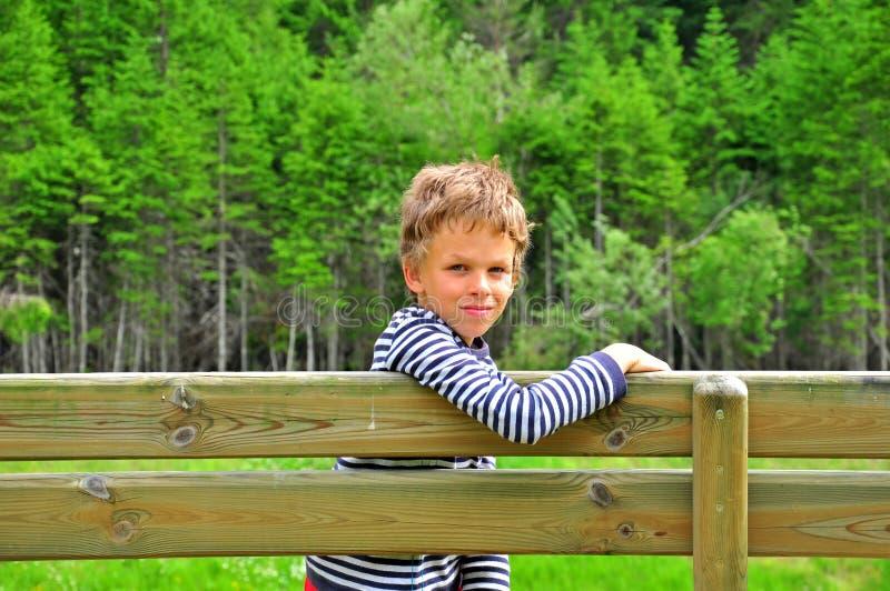 Jongen op een houten bank stock fotografie