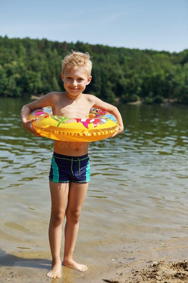 Jongen op een kust met een floting ring in de zomer stock foto