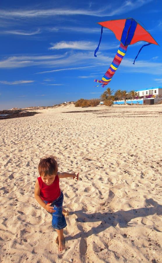 Jongen op een strand met een vlieger royalty-vrije stock afbeeldingen