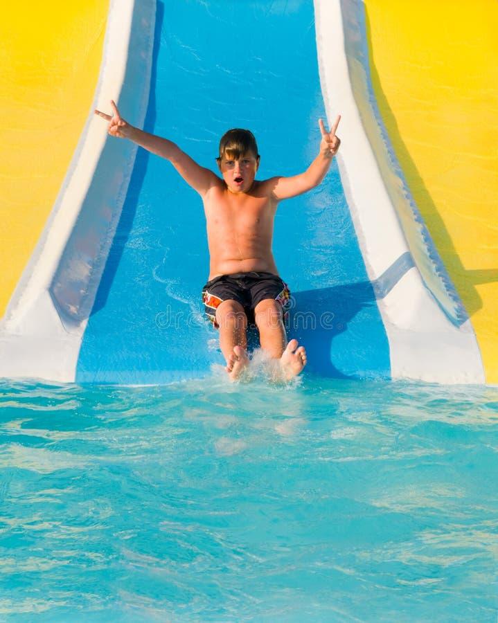 Jongen op een waterslide. royalty-vrije stock afbeeldingen