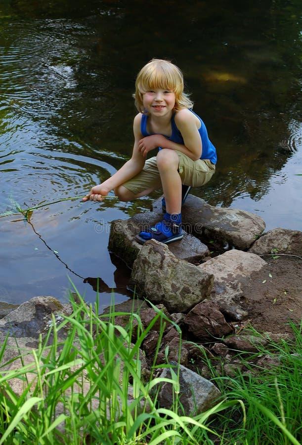 Jongen op rivier stock fotografie