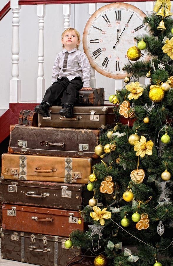Jongen op stapel van koffers bij Kerstmisboom stock afbeeldingen