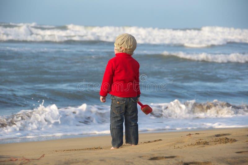Jongen op strand met spade stock foto's