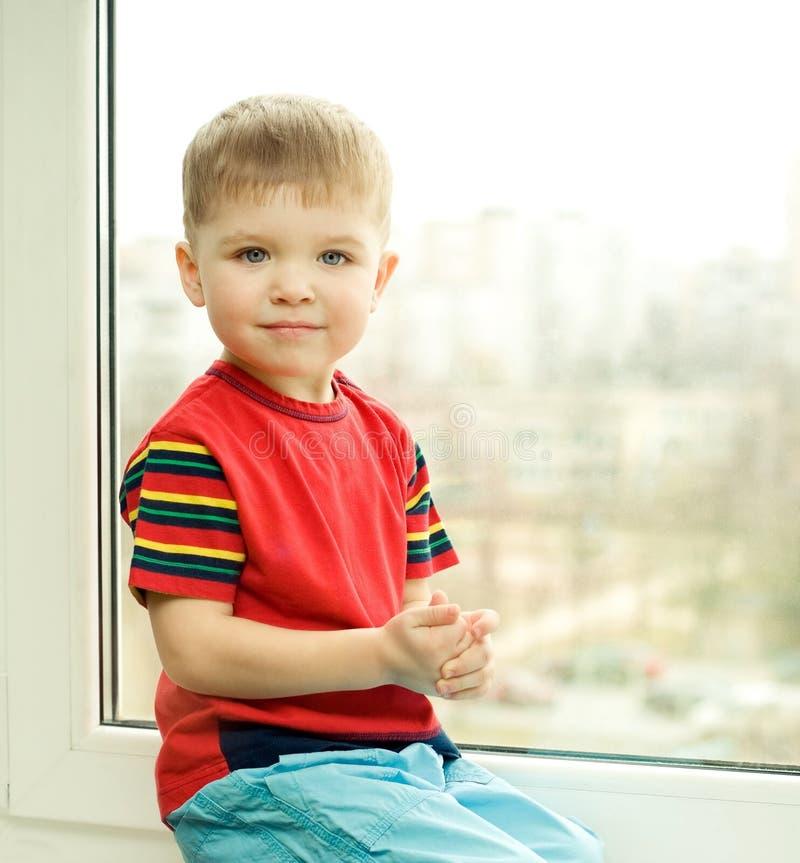 Jongen op venster stock foto