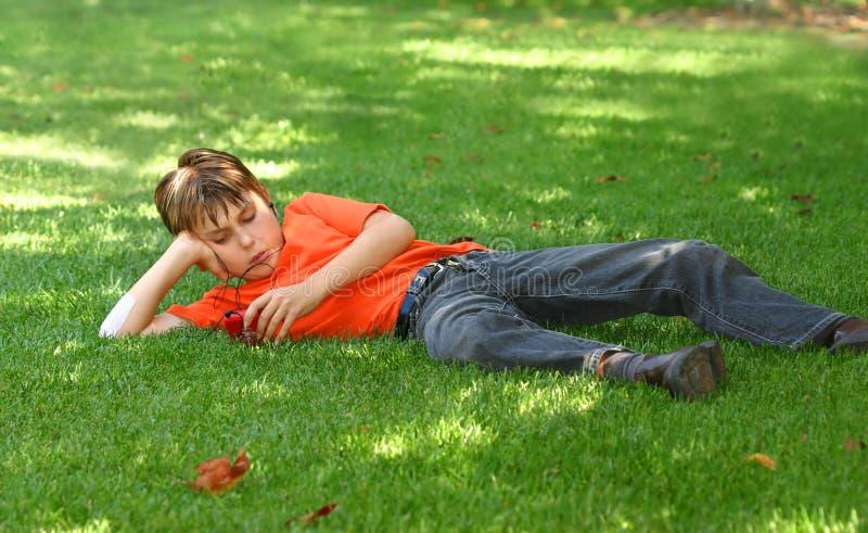 Jongen in park met mp3 speler stock foto's