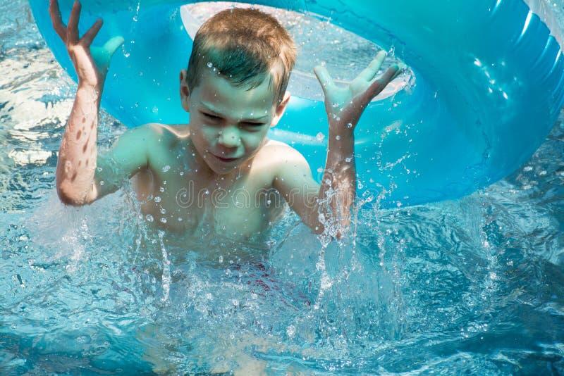 Jongen in pool het bespatten royalty-vrije stock afbeeldingen
