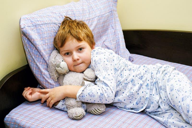Jongen in pyjama's die in bed met zacht stuk speelgoed liggen royalty-vrije stock fotografie