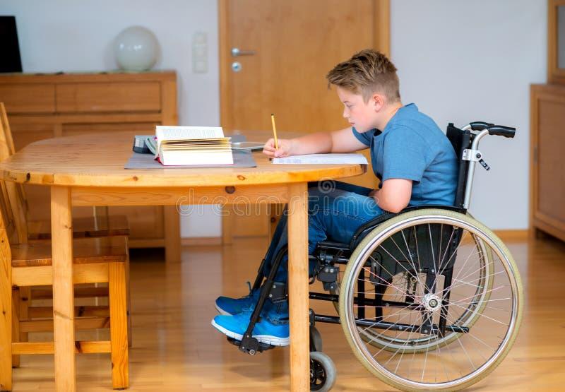Jongen in rolstoel die thuiswerk doen stock foto
