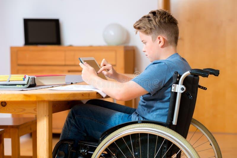 Jongen in rolstoel die thuiswerk doen en tabletpc met behulp van stock fotografie