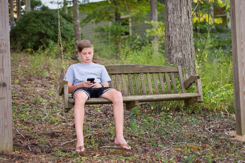 Jongen in Schommeling die of op Telefoon spelen texting stock foto's